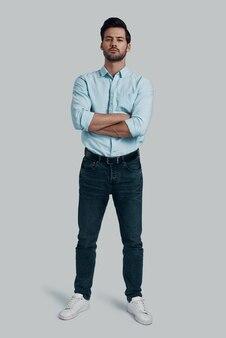 Męskość. pełna długość przystojnego młodego mężczyzny patrzącego w kamerę i trzymającego skrzyżowane ręce, stojąc na szarym tle