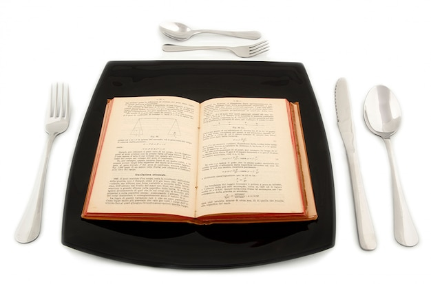 Metaforyczna koncepcja z książką fizyki na talerzu ze sztućcami