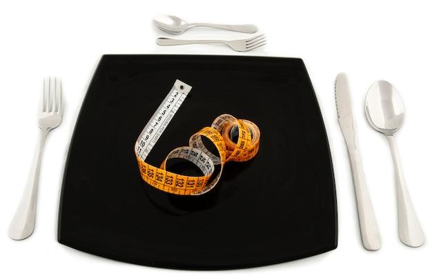 Metaforyczne pojęcie z centymetrem w talerzu ze sztućcami