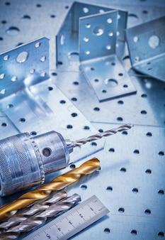 Metal władcy świderu kawałków i kąta bary na dziurkowatym kruszcowym tło budowy pojęciu