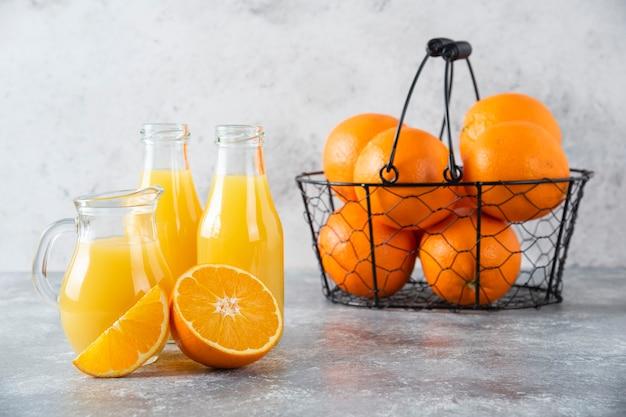 Metaliczny czarny kosz pełen soczystych pomarańczy na kamiennym stole.