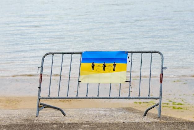 Metalowa bariera z plakatem utrzymuje odległość 2 metrów zainstalowana na plaży