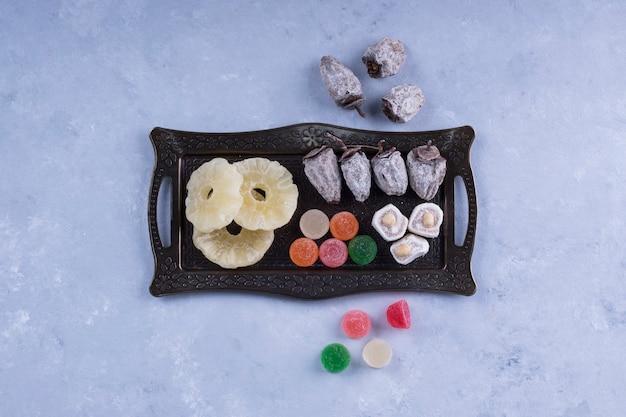 Metalowa deska z przekąskami z suszonymi owocami i marmoladą