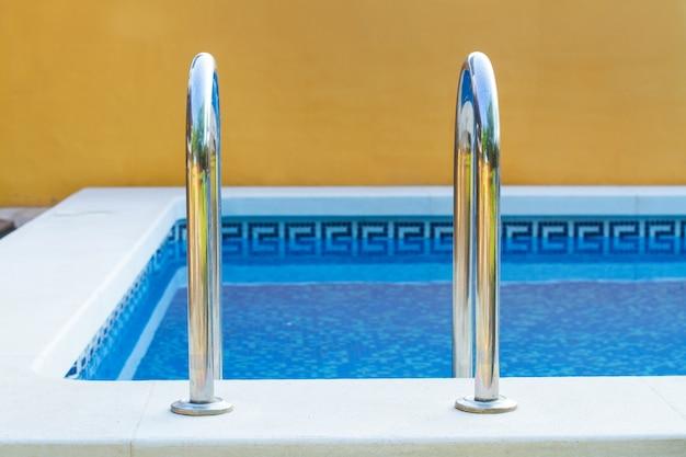 Metalowa drabinka basenowa na szczycie basenu z przezroczystą wodą