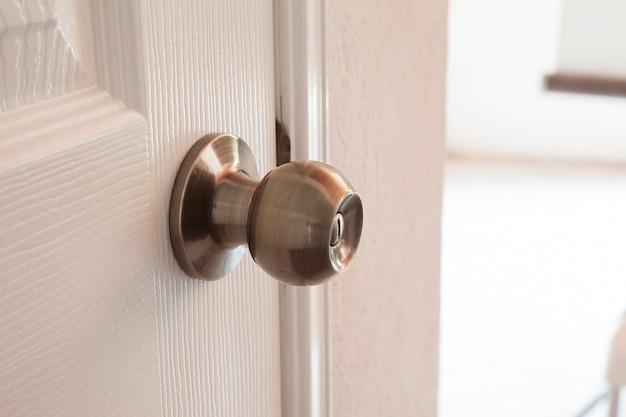 Metalowa gałka na białym tle na białych drzwiach