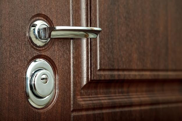 Metalowa klamka i drzwi z chromowaną klamką, zamek. użyj swoich kluczy, aby zamknąć brązowe teksturowane drzwi. dziurka od klucza i klamka z bliska. koncepcja zamkniętych drzwi do mieszkania lub biura projektowego. kopiuj witrynę przestrzeni