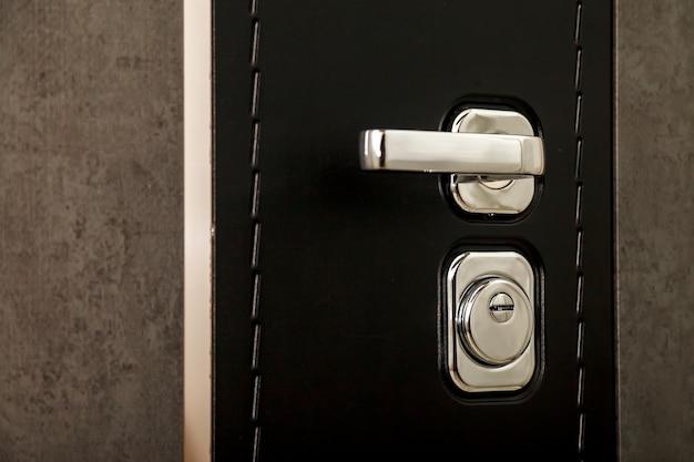 Metalowa klamka i zamek. użyj swoich kluczy, aby zablokować czarne teksturowane drzwi. dziurka od klucza i klamka z bliska. szaro-czarne drzwi z chromowaną klamką i dziurką od klucza. miejsce na twój tekst lub logo