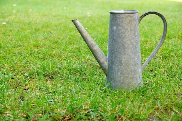 Metalowa konewka na trawiastym polu w ciągu dnia