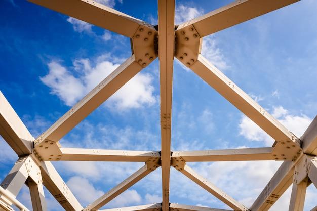 Metalowa konstrukcja belek połączonych śrubami na tle nieba.