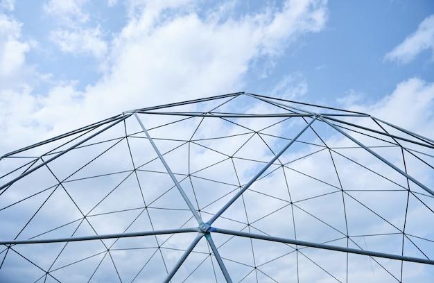 Metalowa konstrukcja na tle błękitnego nieba z białymi chmurami.