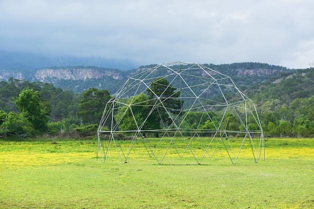 Metalowa konstrukcja na zielonej trawie i niebieskim niebie.