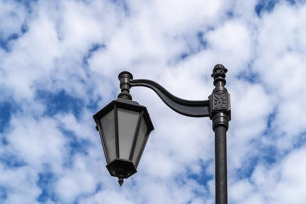 Metalowa latarnia uliczna w klasycznym stylu na tle błękitnego nieba.