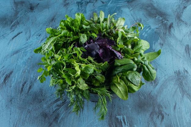 Metalowa miska świeżych zdrowych zielonych liści na niebieskiej powierzchni.