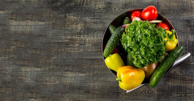 Metalowa miska ze świeżymi ziołami i asortymentem surowych warzyw na banner rustykalny stół z drewna