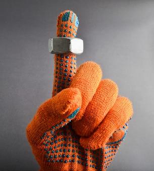 Metalowa nakrętka na palcu wskazującym z pomarańczowymi rękawiczkami roboczymi