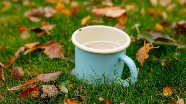 Metalowa niebieska filiżanka z kawą na zielonej trawie z liśćmi w sezonie jesiennym