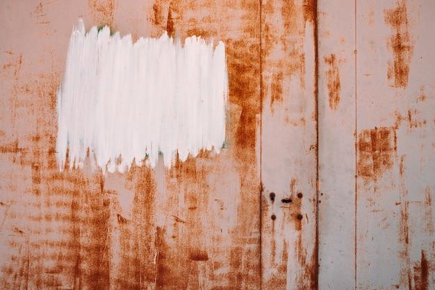 Metalowa powierzchnia rdzy. tło częściowo zardzewiały. szorstki talerz tlenkowy. białe lakierowane miejsce. tekstura twardego rozkładu. utlenianie stali. częściowo zardzewiały metalowy panel. odpadająca farba.