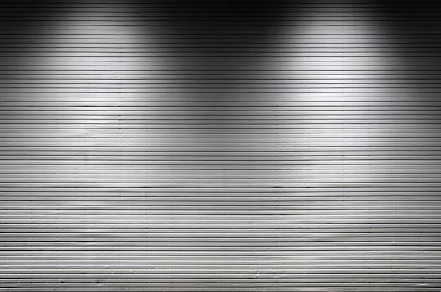 Metalowa ściana z niewidocznymi źródłami światła, które oświetlają środek do umieszczenia produktu