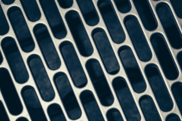 Metalowa siatka z prostokątną perforacją z zaokrąglonymi krawędziami.