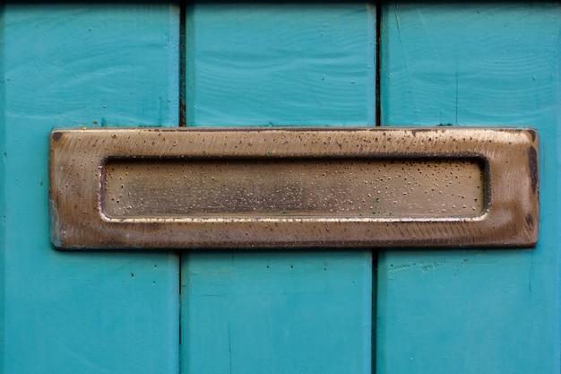 Metalowa skrzynka na listy na drewnianych drzwiach malowanych na niebiesko. obraz retro