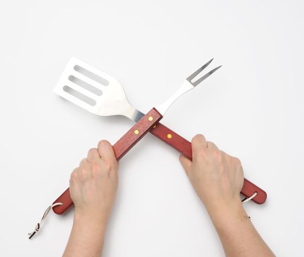 Metalowa szpatułka i widelec z drewnianą rączką na piknik w kobiecej dłoni z pomalowanymi czerwonymi paznokciami na białym tle, sztućce skrzyżowane