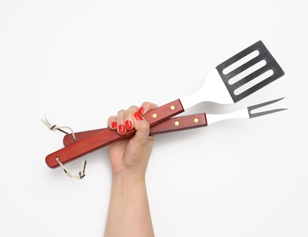 Metalowa szpatułka i widelec z drewnianą rączką na piknik w kobiecej dłoni z pomalowanymi czerwonymi paznokciami na białym tle