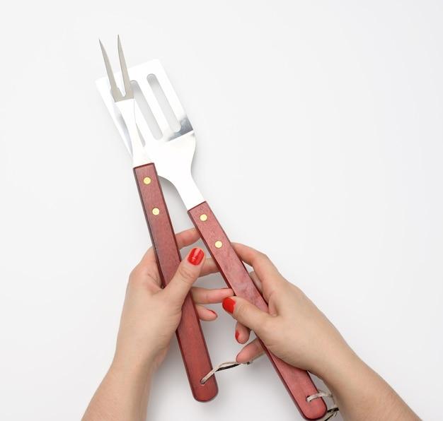 Metalowa szpatułka z drewnianą rączką i widelcem na piknik w kobiecej dłoni z pomalowanymi czerwonymi paznokciami na białym tle