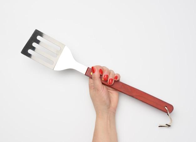 Metalowa szpatułka z drewnianym uchwytem na piknik w kobiecej dłoni z pomalowanymi czerwonymi paznokciami na białym tle
