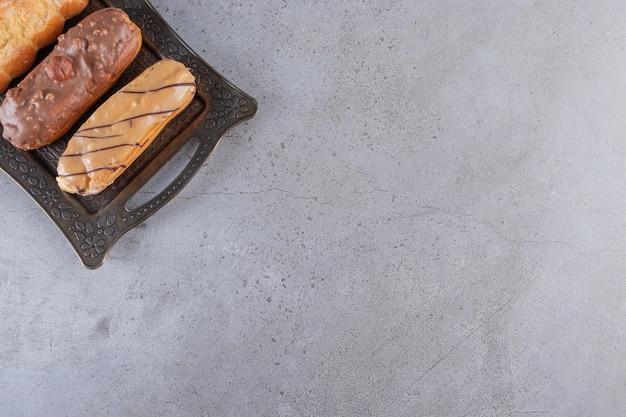 Metalowa taca słodkich smacznych eklerów na kamiennym stole.