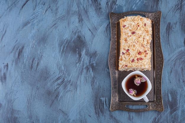 Metalowa taca z tortem owocowym i filiżanką czarnej herbaty na marmurowym tle.