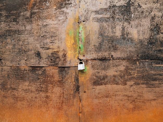 Metalowa zardzewiała brama i kłódka