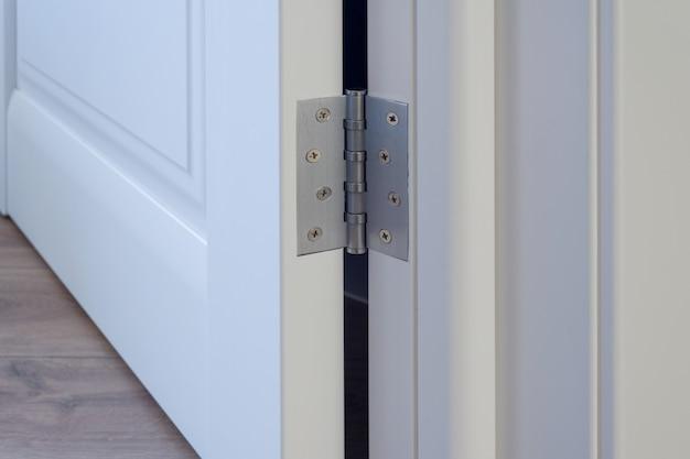 Metalowe chromowane zawiasy na białych drzwiach wewnętrznych