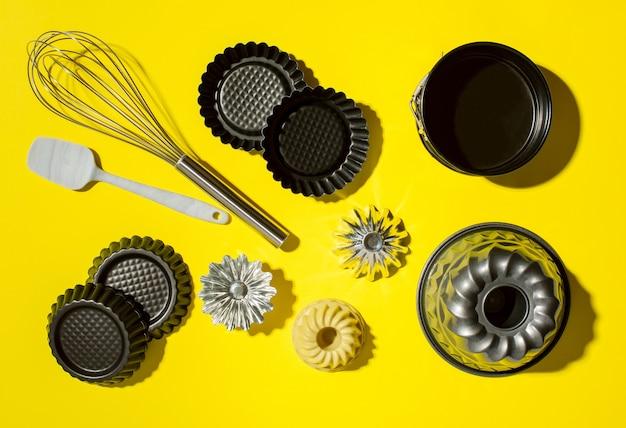 Metalowe formy do babeczek i ubijaj naczynia kuchenne do pieczenia metalowych kształtów na żółtym tle