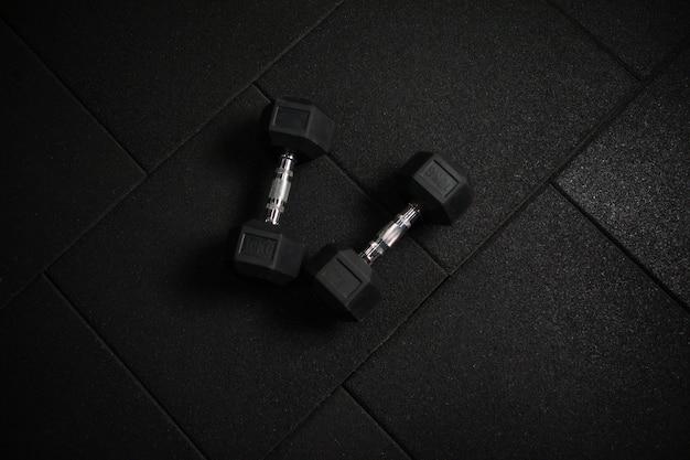 Metalowe gumowane hantle na ciemnej, czarnej podłodze. kulturystyka i fitness