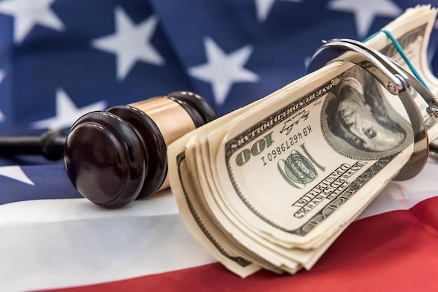 Metalowe kajdanki, młotek sędziów i banknoty dolarowe leżące na fladze amerykańskiej