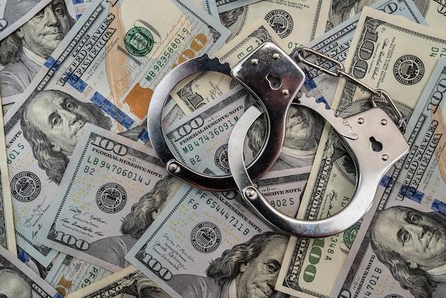 Metalowe kajdanki na banknotach stu dolarowych