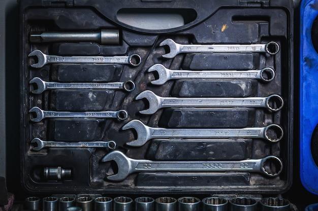 Metalowe klucze o płaskich rozmiarach różnych rozmiarów znajdują się w skrzynce narzędziowej, widok z góry.