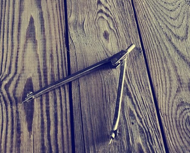 Metalowe kompasy na drewnianym stole.