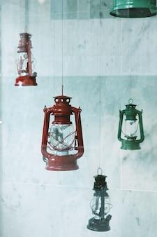 Metalowe latarnie gazowe w różnych kolorach, wiszące w pobliżu ściany z płytek