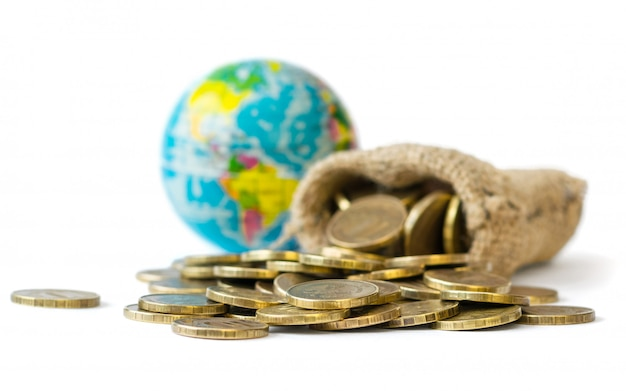 Metalowe monety wylane z torby i kuli ziemskiej