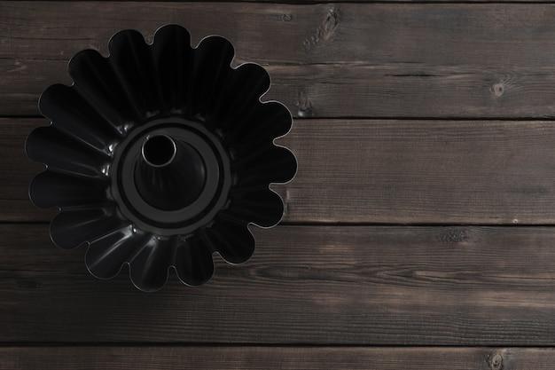 Metalowe naczynie do pieczenia ciasta na drewnianej ścianie