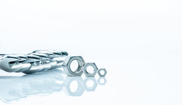 Metalowe nakrętki sześciokątne i klucze chromowane na białym tle. narzędzia mechaniczne do konserwacji. narzędzie sprzętowe. zapięcie z gwintowanym otworem. ustaw chromowany klucz nasadowy i nakrętki.