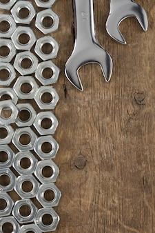 Metalowe narzędzie do nakrętek i klucza na drewnianej ścianie tekstury