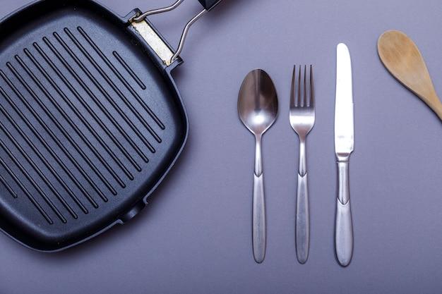 Metalowe noże z czernią na szarym stole, patelnia do grillowania, ręcznik. układ płaski, układ.