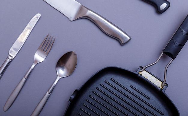 Metalowe noże z czernią na szarym stole, patelnia do grillowania