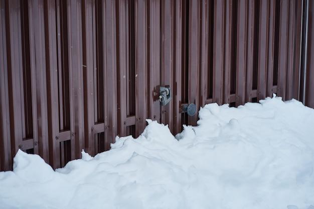 Metalowe ogrodzenie i śnieg na wsi, brama z kłódką, widok z boku