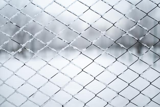 Metalowe ogrodzenie przewodowe pod śniegiem - tekstura tło.