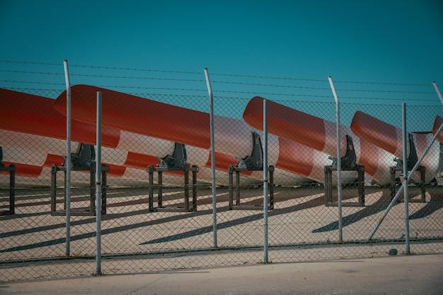 Metalowe ogrodzenie z drutu kolczastego i metalowe kajaki za nim z niebieskim niebem