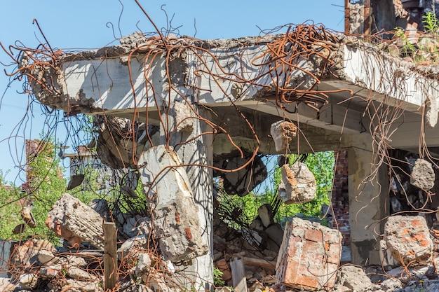 Metalowe okucia zardzewiały drut wkręcony w nakładający się stary budynek.