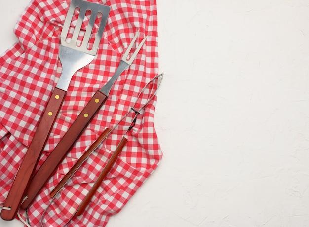 Metalowe przybory kuchenne z drewnianymi uchwytami do grilla na białym tle, kopia przestrzeń